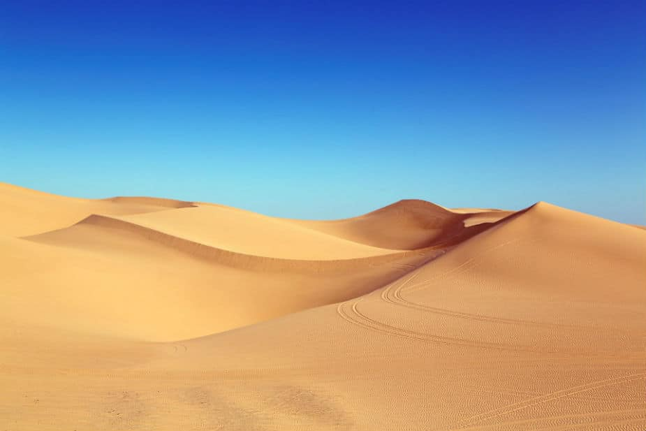 This is an image of sand dunes agains a blue sky. The image has a large size.