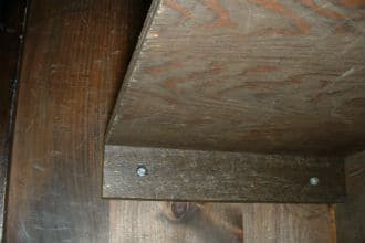 This shows a simple way to support a shelf. A wood piece is screwed into a side supporting piece in order to hold the shelf. The screws in the side piece are countersunk. Small image.