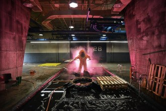 This picture shows a man in a hazmat suit cleaning pallets