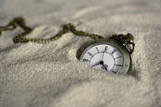 This shows a pocket watch resting on sand. Image is from the How Long To Let Wood Glue Dry Before Sanding blog article.
