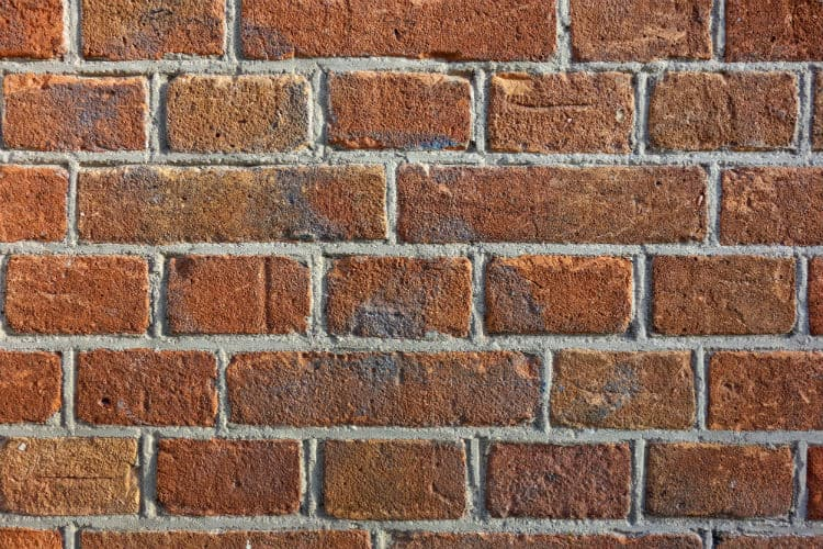 This image shows red bricks held by mortar. It symbolizes the brick and mortar store.