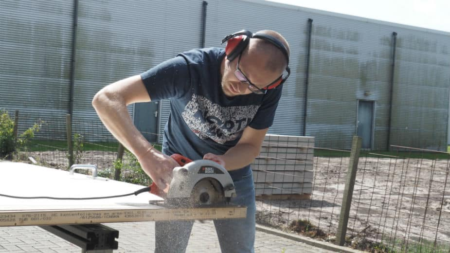 This image shows a man working with a circular saw.