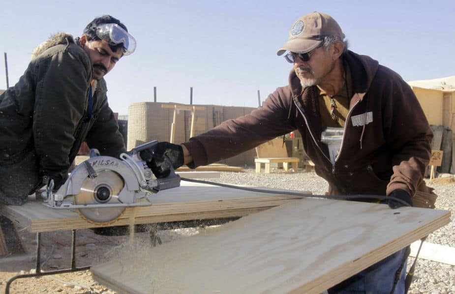 This image shows men working with a circular saw.
