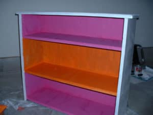 Wooden bookcase with orange and magenta paint