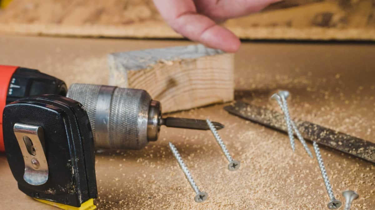 A hand throws wood screws through the air. A drill is in the background.