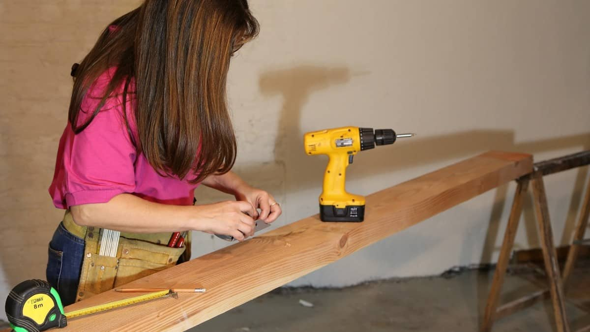 woman with drill and measuring tape